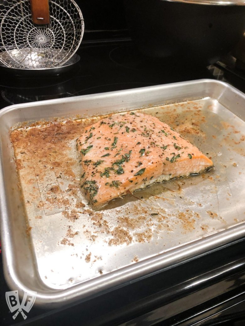 3/4 view of roasted salmon on a baking sheet.