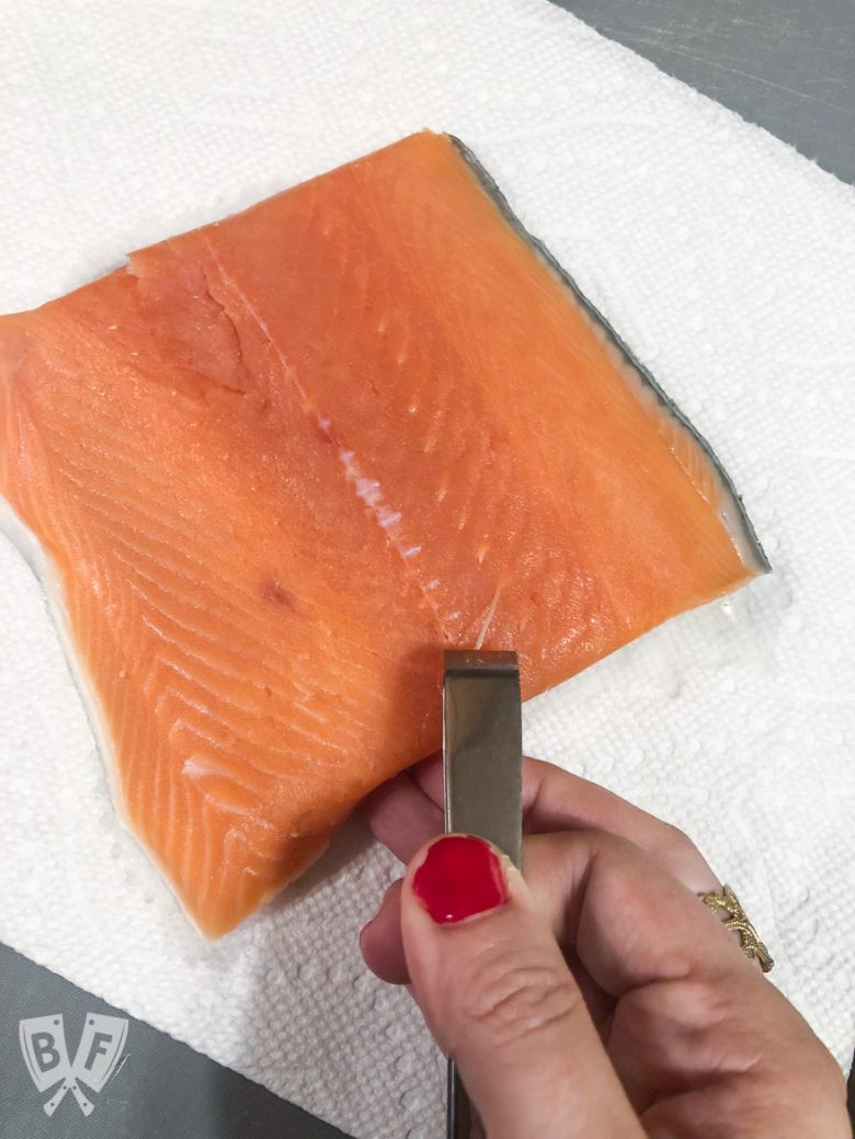 Overhead view of pin bones being removed from a king salmon fillet.