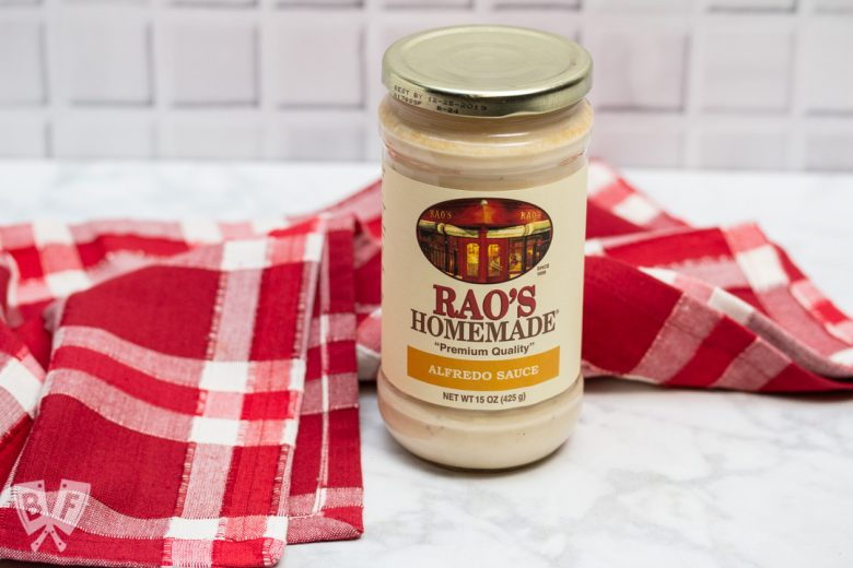 A jar of alfredo sauce in front of a red and white checkered cloth.