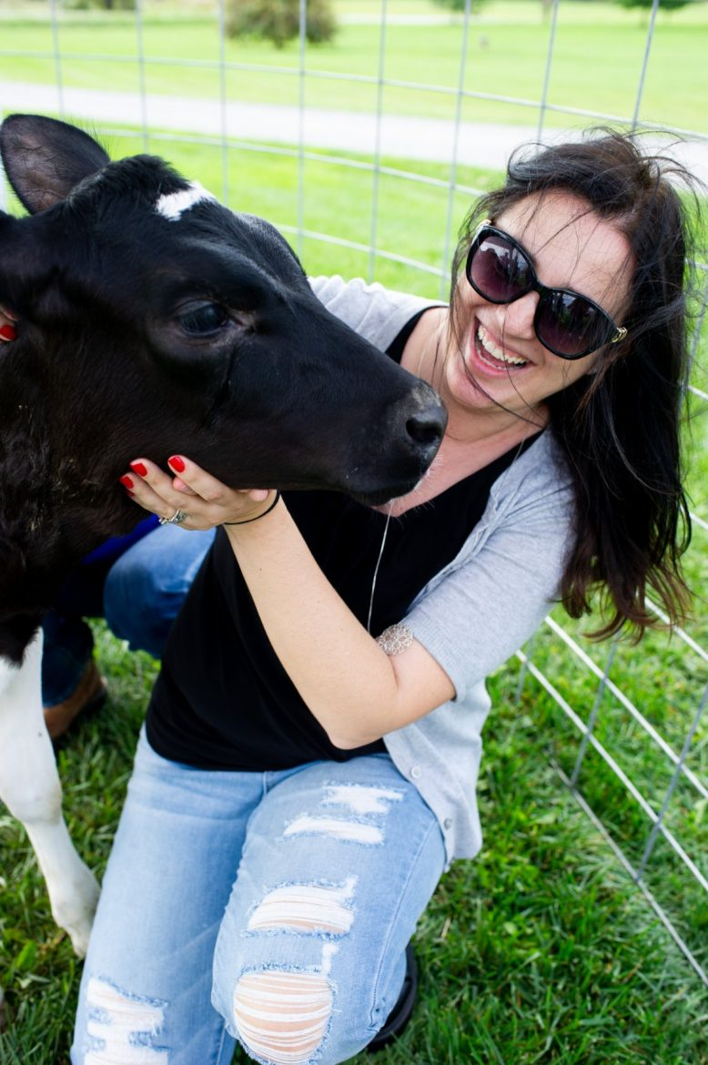 A food blogger snuggling with a baby cow on the farm.