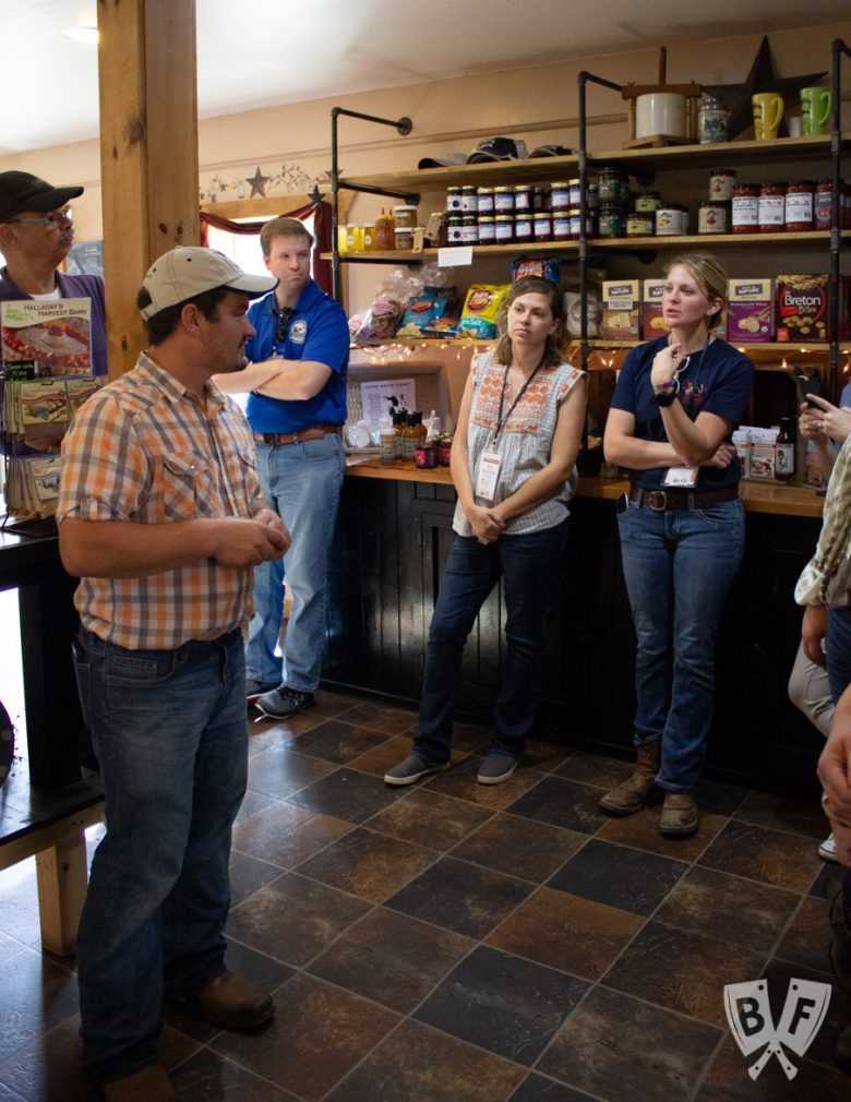 A farmer talking to a group of people inside the farm shop.