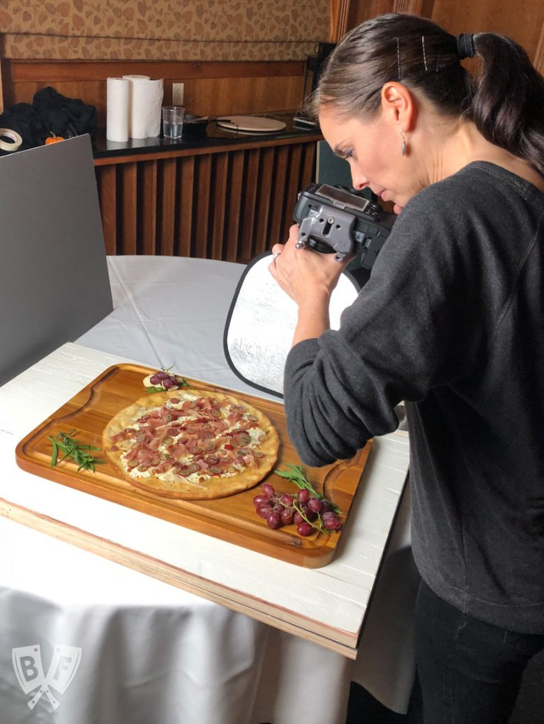 A photographer shooting photos of a burrata pizza with prosciutto and pickled grapes.