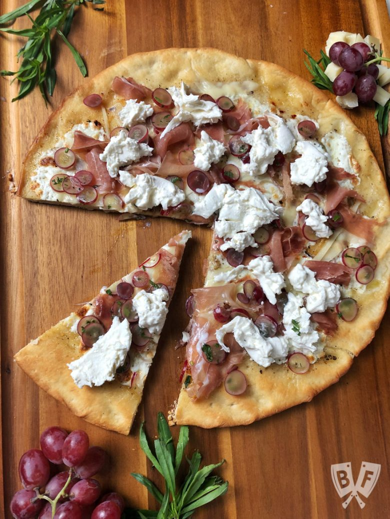Overhead view of Burrata Pizza with Prosciutto and Pickled Grapes.