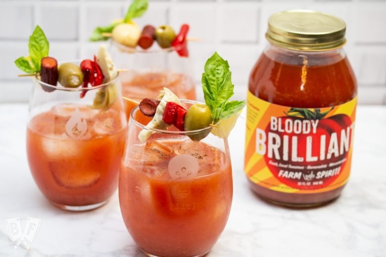 Side view of 3 Bloody Mary cocktails garnished with Italian antipasto ingredients next to a jar of Bloody Mary mix.