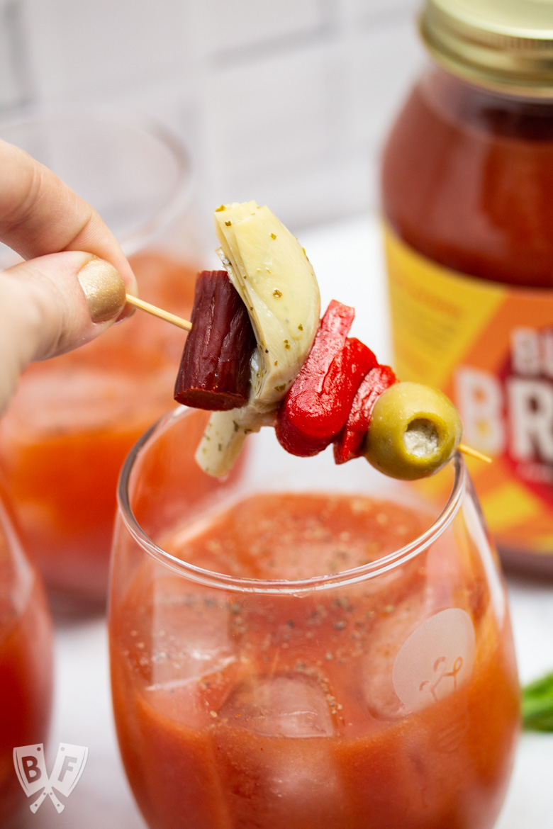 Hand placing a skewer of Italian antipasto ingredients on top of a Bloody Mary cocktail.