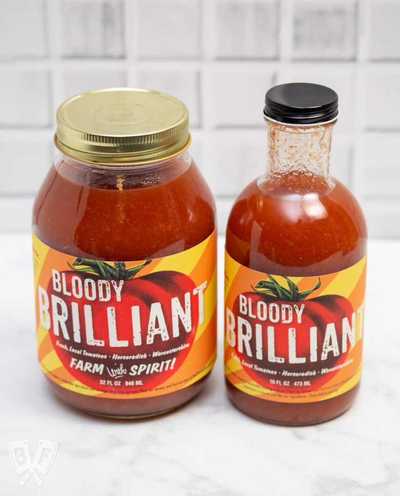 Side view of a jar and a bottle of Bloody Mary mix.