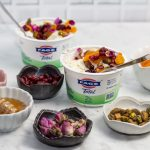 3/4 view of yogurt cups with an array of Persian toppings for making jeweled yogurt parfaits.