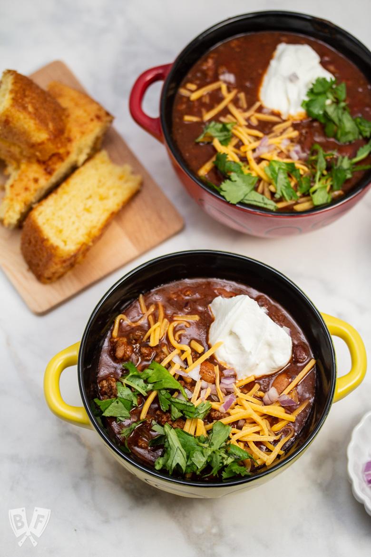 Overhead shot of 2 bowls of spicy turkey three-bean chili with cornbread.