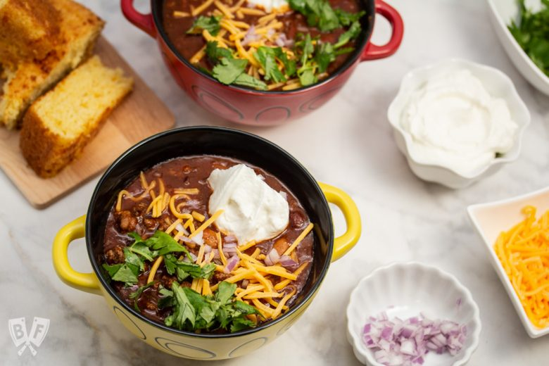 Overhead view of bowls of Spicy Turkey Three-Bean Chili with toppings and cornbread alongside.