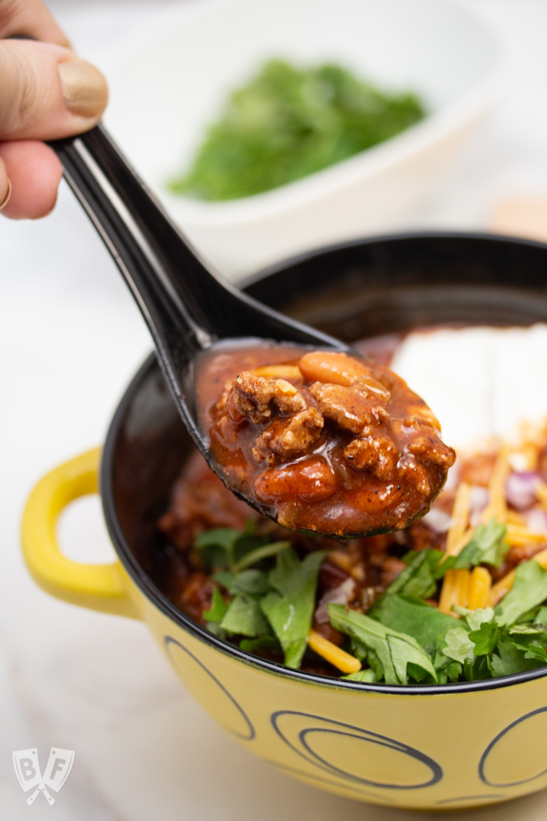 Close up of a spoonful of Spicy Turkey Three-Bean Chili being lifted from a bowl.