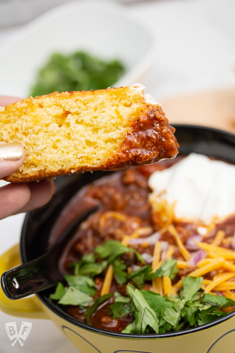 Hand dipping a wedge of cornbread into a bowl of Spicy Turkey Three-Bean Chili