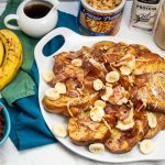 Overhead view of French toast with bananas, bacon, peanut butter, and topping alongside.