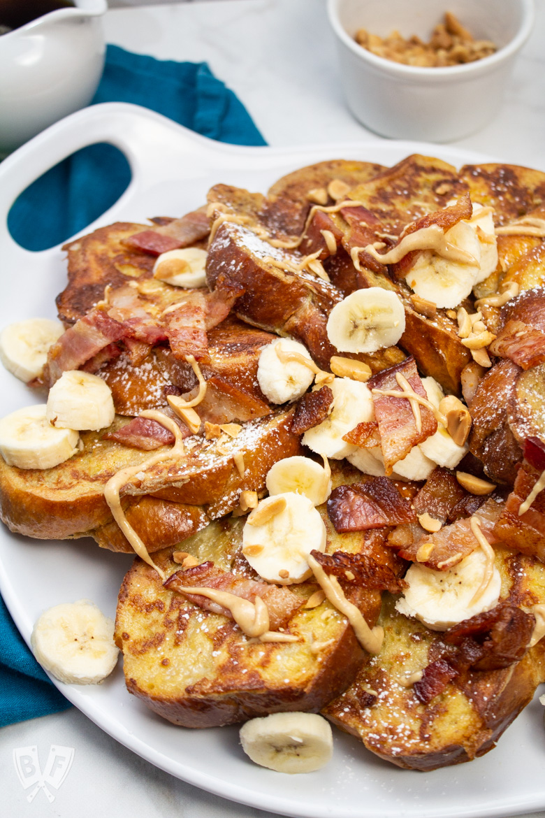Platter of challah French toast with bacon, banana, and peanut butter.