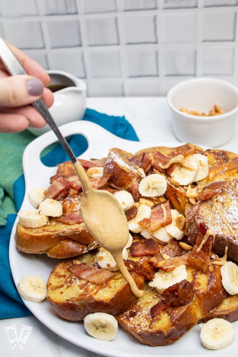 Hand drizzling peanut butter onto a platter of Elvis-Style Challah French Toast
