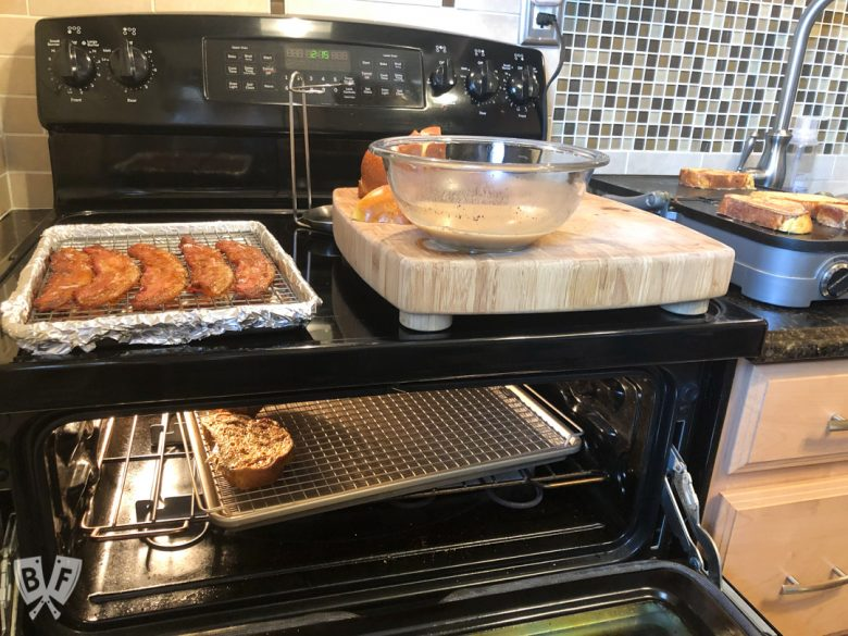An oven and a griddle in the process of cooking bacon and French toast.