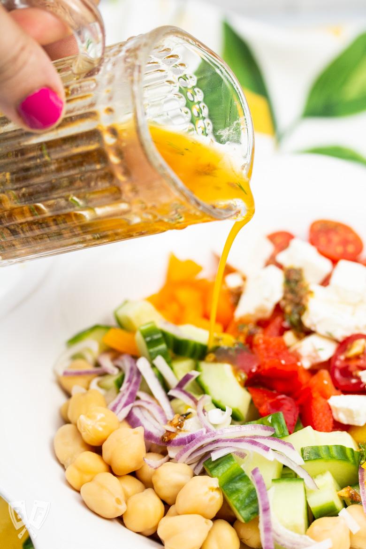 Pouring vinaigrette onto Mediterranean Chickpea Salad with Lemon-Herb Vinaigrette
