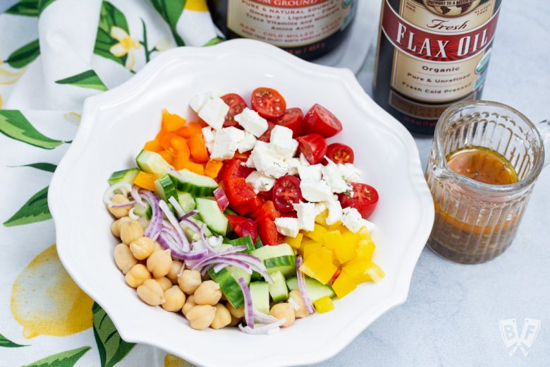 Overhead view of a bowl of Mediterranean Chickpea Salad with Lemon-Herb Vinaigrette with dressing and ingredients to the side