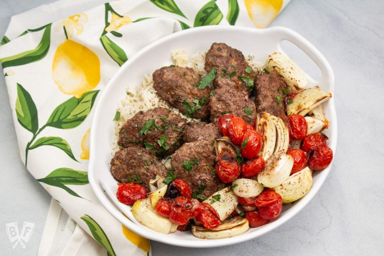 Overhead view of a platter of kebab with onions and tomatoes.