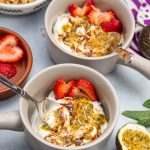 Overhead view of Greek yogurt parfaits with colorful tropical fruit toppings.