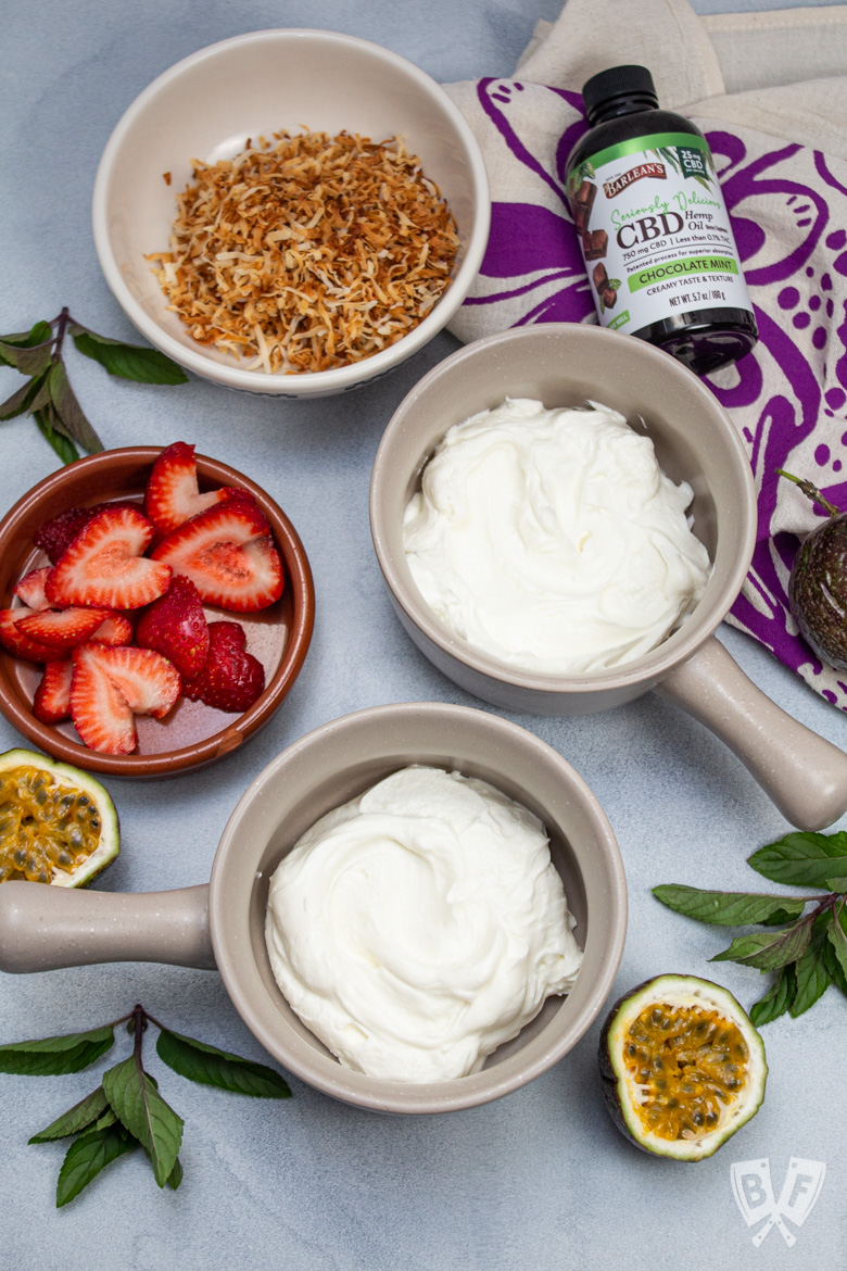 Overhead view of bowls of Greek yogurt with tropical fruit and chocolate mint CBD oil alongside.
