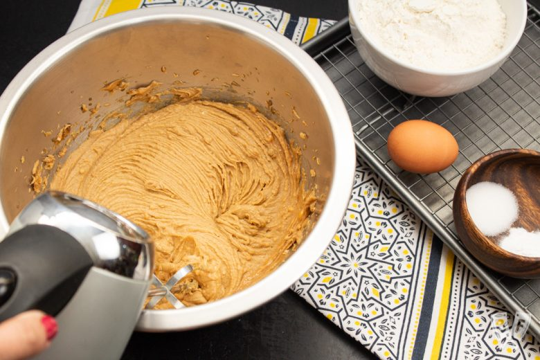 Creaming ingredients for peanut butter cookies with a hand mixer