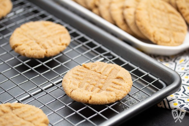 Peanut butter cookies cooling on a baking sheet