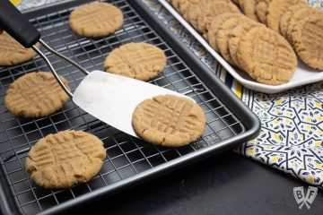 Spatula removing a peanut butter cookie from a baking sheet