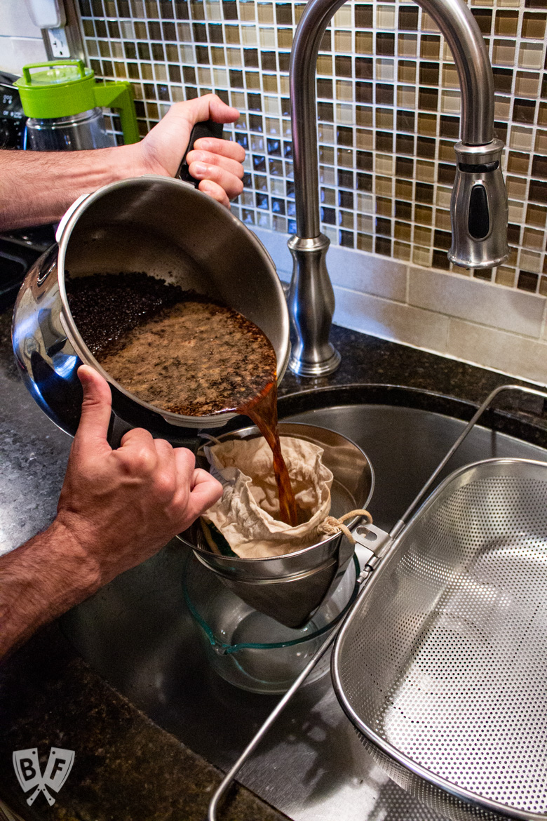 Straining a batch of cold brew coffee
