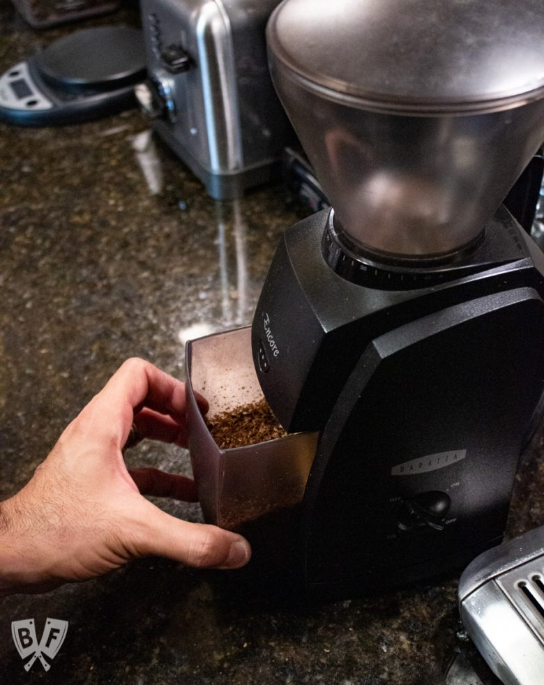 Removing a container of freshly ground coffee beans from a burr grinder to make cold brew coffee