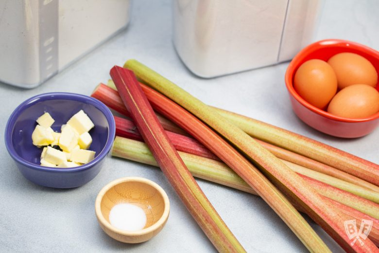 Stalks of rhubarb with butter, flour, sugar, salt, and eggs for making pie