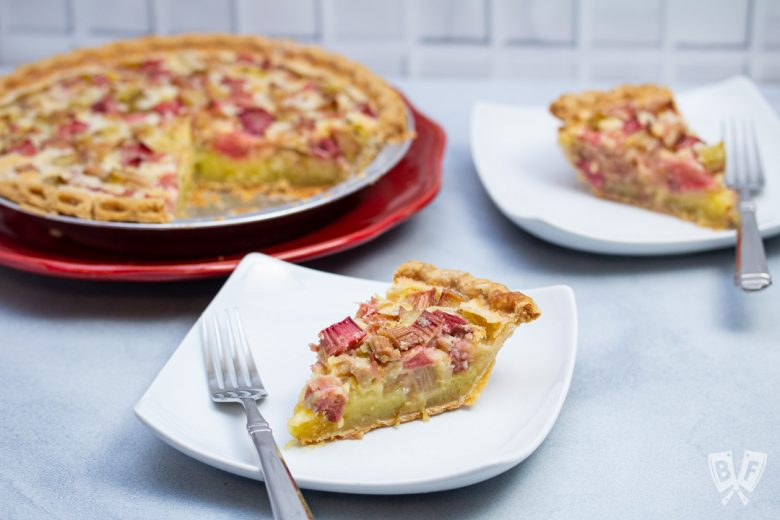 A rhubarb custard pie with plated slices and forks