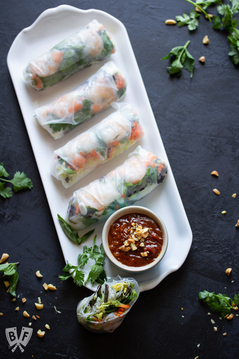 Platter of Vietnamese fresh spring rolls with shrimp and peanut dipping sauce and ingredients sprinkled around.