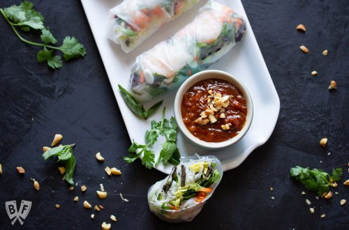 Platter of Vietnamese fresh spring rolls with shrimp & peanut sauce surrounded by ingredients.