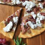 Overhead view of a slice cut out of a Burrata Pizza with Prosciutto and Pickled Grapes