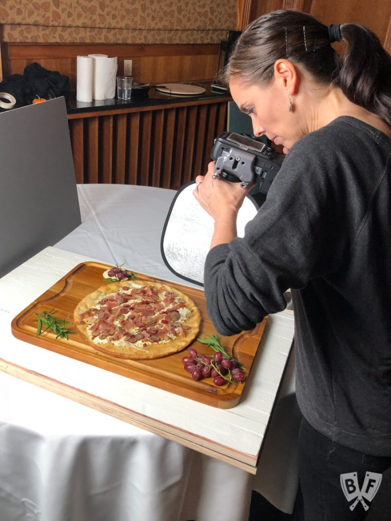 Photographer shooting photos of Burrata Pizza with Prosciutto and Pickled Grapes
