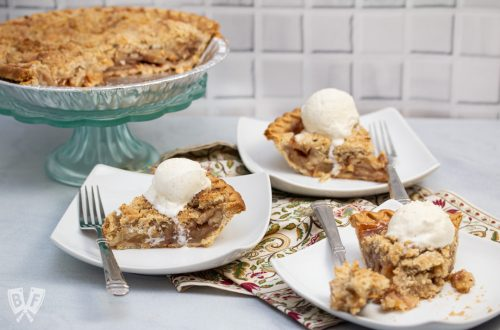 Plates with slices of Dutch apple pie topped with ice cream