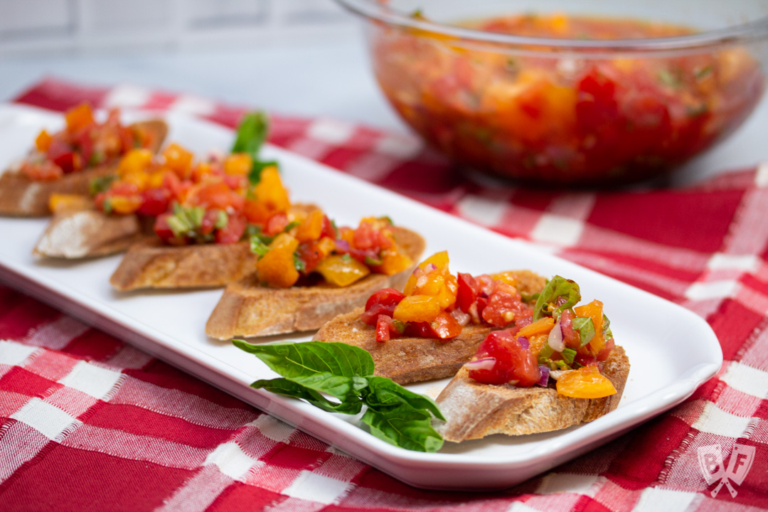 Platter of Italian Bruschetta with bowl of tomato mixture in the background