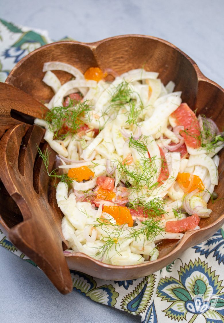 Bowl of fennel citrus salad with salad hand tools to the side.