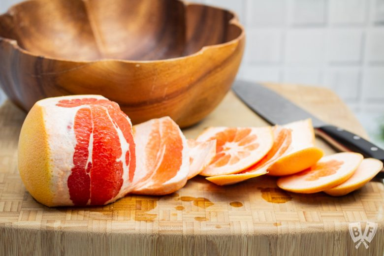 Cutting the rind off of a grapefruit.