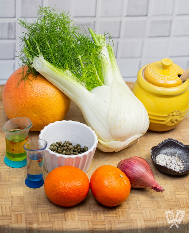 Ingredients for fennel and citrus salad with shallots and capers out on a cutting board.