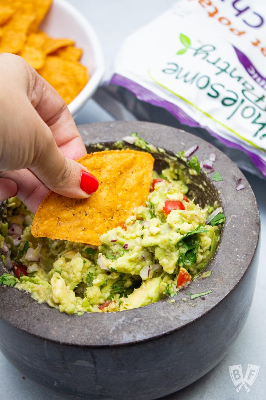 Dipping a tortilla chip into guacamole.