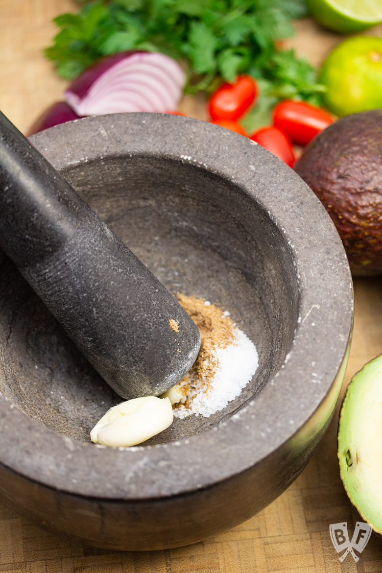 Smashing garlic and spices with a mortar and pestle for restaurant-style guacamole.