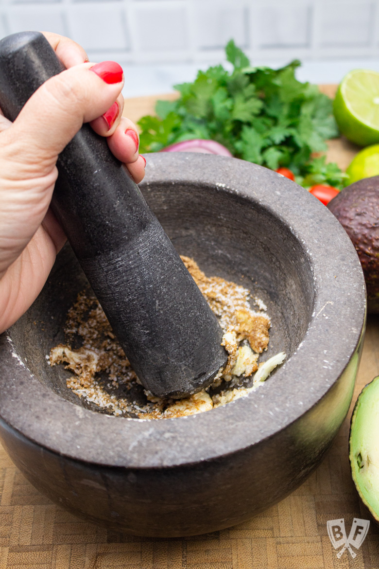 Smashing garlic and spices with a mortar and pestle.