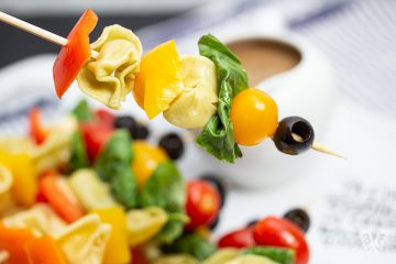 Skewer with tortellini, bell peppers, fresh basil, tomatoes, and olives.
