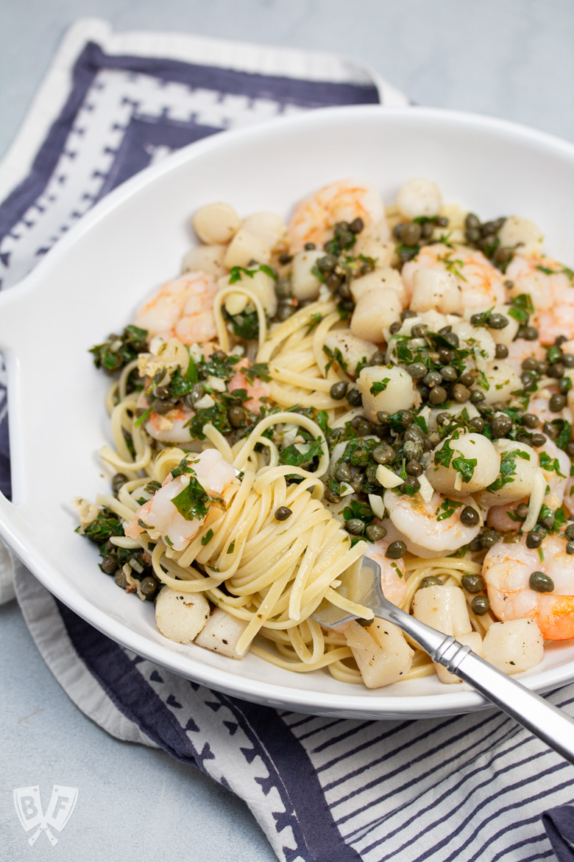 Fork twirling pasta in a bowl of Shrimp + Scallop Linguine with Lemon Caper Butter