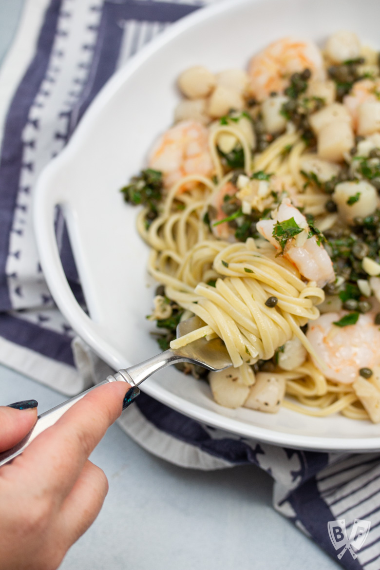 Fork twirling linguine in a bowl with shrimp and scallops.