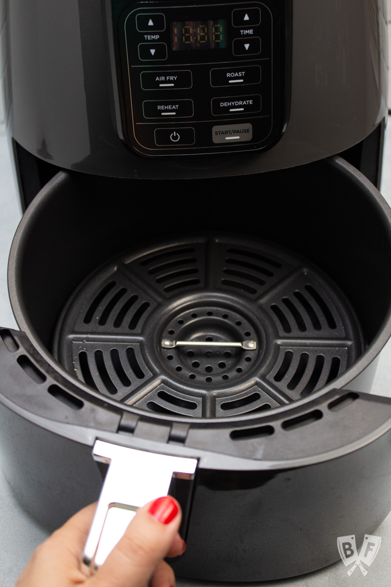 Pulling the drawer out of a Ninja air fryer.