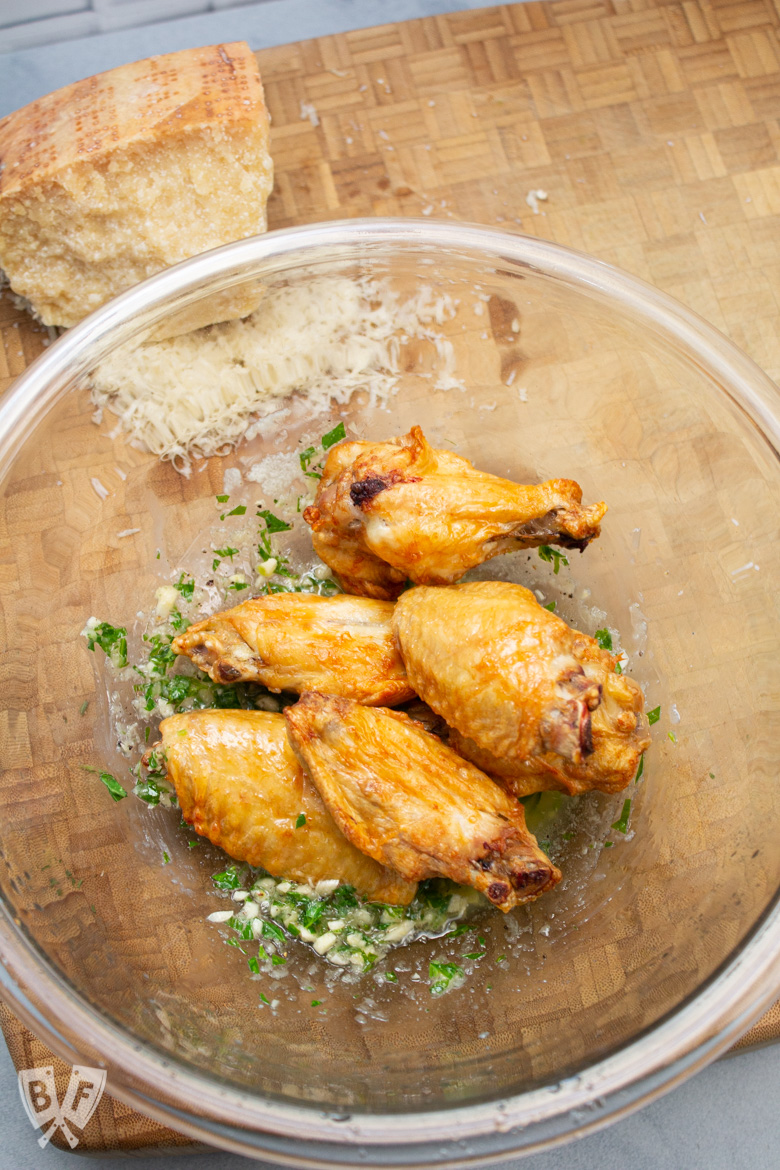 Bowl of air fried chicken wings on top of garlic Parmesan sauce