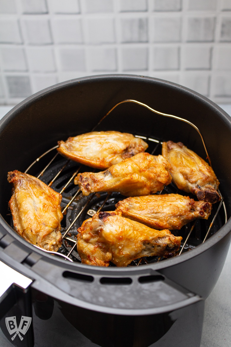 Air fryer tray with cooked chicken wings on the rack