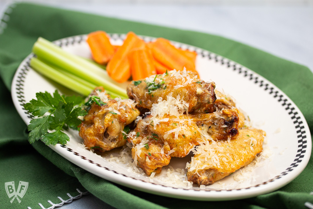 Plate of air fryer garlic parmesan chicken wings with carrots and celery.